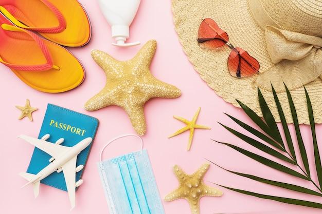 Composizione piatta con accessori per vacanze al mare giocattolo aereo e passaporto su sfondo colorato