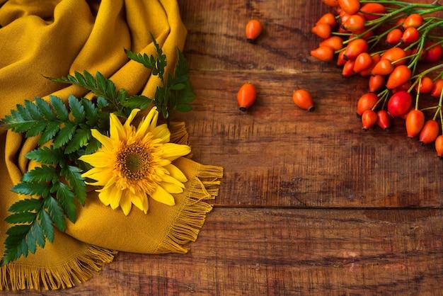 Una composizione piatta con una sciarpa lavorata a maglia gialla, un ramoscello verde, cinorrodi e girasole su un tavolo di legno. accogliente autunno o il concetto di riposo invernale. posto per testo, cornice, vista dall'alto, copia spazio, layout
