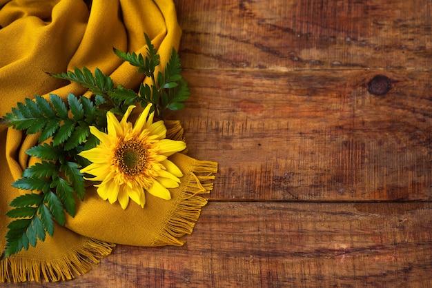 Composizione piatta con sciarpa lavorata a maglia gialla, ramoscello verde e girasole su un tavolo di legno
