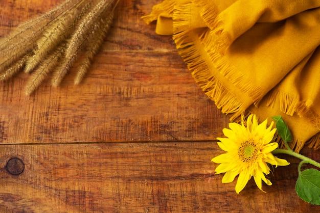 Composizione piatta con sciarpa lavorata a maglia gialla, spighette di grano e girasole su un tavolo di legno. accogliente autunno o il concetto di riposo invernale. posto per testo, cornice, vista dall'alto, copia spazio, layout