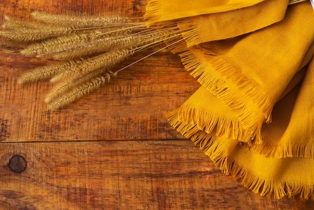Composizione piatta con sciarpa lavorata a maglia gialla e spighette di grano su un tavolo di legno. accogliente autunno o il concetto di riposo invernale. posto per testo, cornice, vista dall'alto, copia spazio, layout