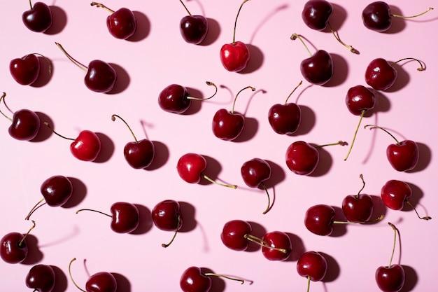 Lat piatto di ciliegie su sfondo rosa e ombre dure