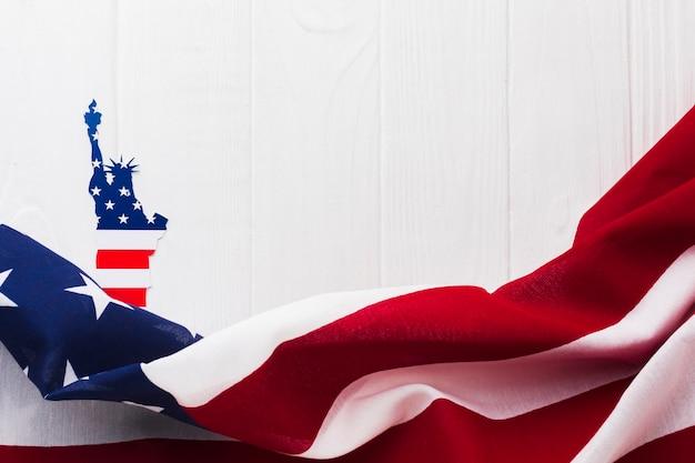 Disposizione piana della bandiera americana per la festa dell'indipendenza con la statua della libertà