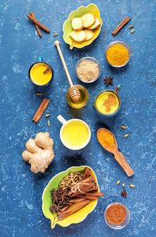 Disposizione piana di tazze di latte di curcuma dorata e ingredienti per la sua cottura su sfondo blu. foto verticale.