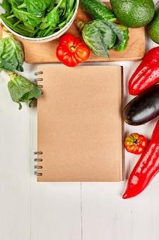 Lay piatto di verdure assortite intorno al libro di ricette di cucina