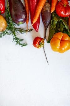 Piatto disteso di assortimento di verdure fresche, cibo biologico sano e biologico su sfondo bianco, stile mercato country, prodotti dell'orto, cibo vegetariano dietetico, alimentazione pulita