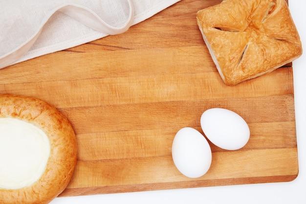 Cottura piatta o cottura. utensili da cucina, ingredienti per cuocere torte e crostate, farina, uova, mattarello, torta con ripieno, cheesecake, grembiule. spazio per il testo