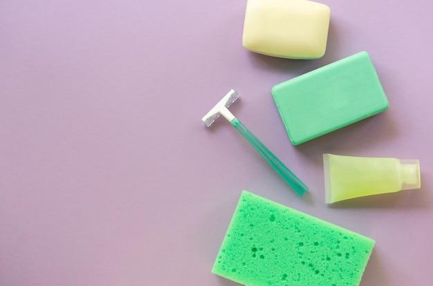 Lay piatto di prodotti per il bagno e l'igiene. rasoio, saponetta e salvietta su fondo lilla. spazio per il testo.