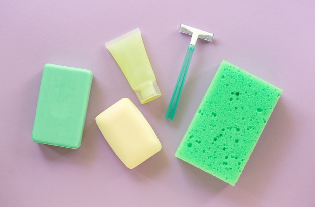 Lay piatto di prodotti per il bagno e l'igiene. rasoio, saponetta e salvietta su fondo lilla.