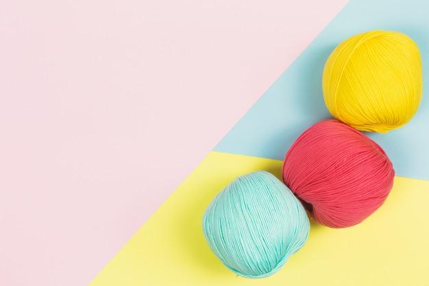 Disposizione piana di belle palle verde menta, rosa corallo e giallo scuro di lana di cotone con colori pastello geometrici sfondo e copia spazio