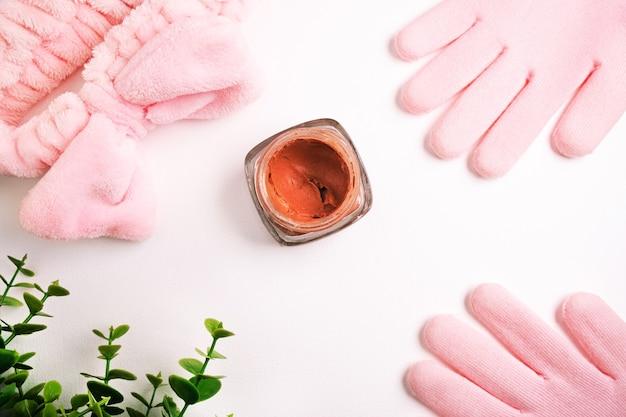 Disposizione piatta di prodotti per la cura della bellezza, corallo o argilla rosa per viso e corpo circondati da accessori di bellezza