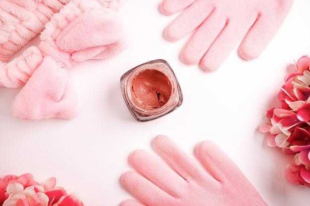 Disposizione piatta di prodotti per la cura della bellezza, viso corallo o rosa e argilla per il corpo circondati da accessori di bellezza.