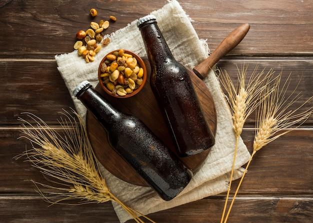 Lay piatto di bottiglie di birra con noci e grano