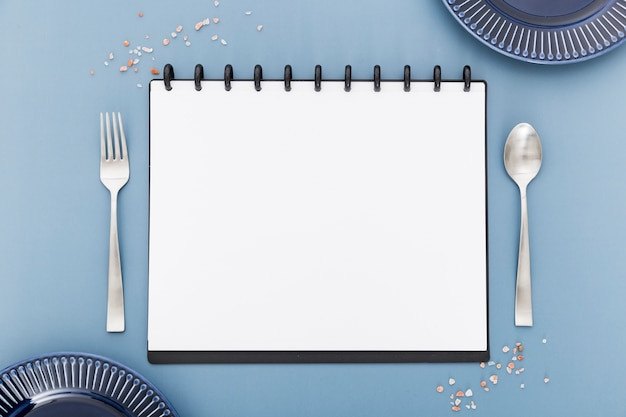 Lay flat di menu vuoto notebook con posate e piatti