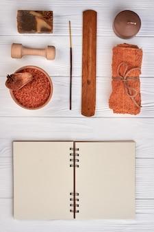 Blocco note vuoto piatto con accessori spa sulla scrivania bianca