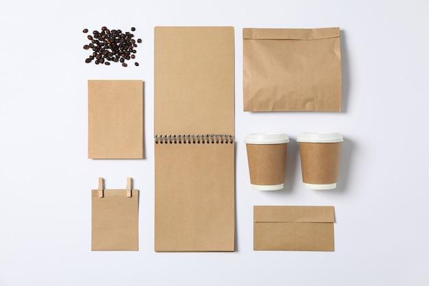 Disteso. cancelleria in bianco, tazze di carta e mazzo di caffè su fondo bianco