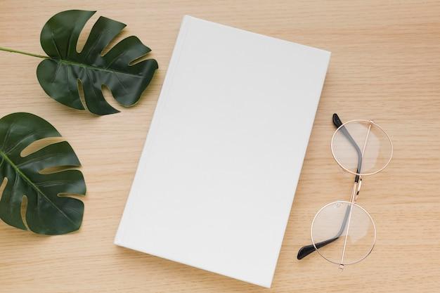Libro piatto disteso sul tavolo con gli occhiali