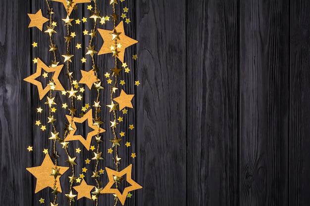 Bordo piatto laici di stelle grandi e piccole di coriandoli. perline dorate a forma di stelle.