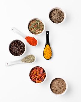 Ciotole piatte e cucchiai con spezie