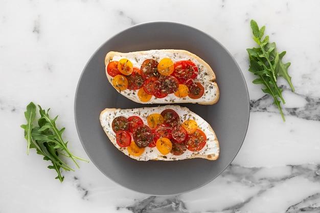 Pane piatto laici con crema di formaggio e pomodorini sul piatto
