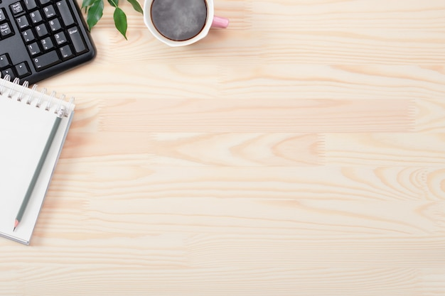 Disposizione piana della scrivania dell'ufficio di affari. tastiera, matita, caffè nero, foglie verdi, taccuino sulla tavola di legno