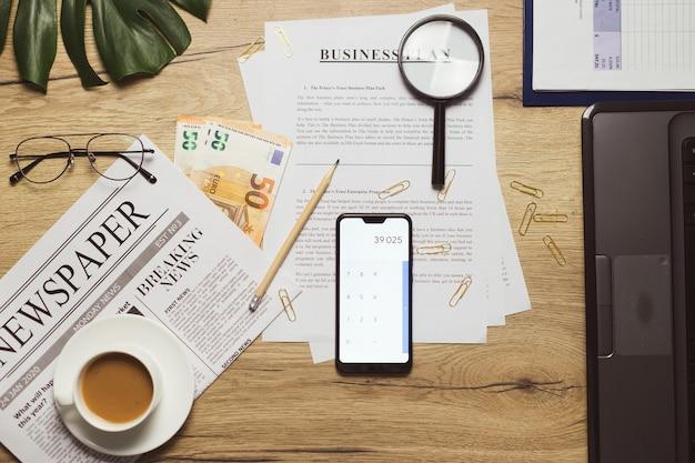 Disposizione piana dei documenti del piano aziendale sul posto di lavoro. soldi, giornali, bicchieri, tazza di caffè, graffetta e forniture sulla scrivania del tavolo in legno.