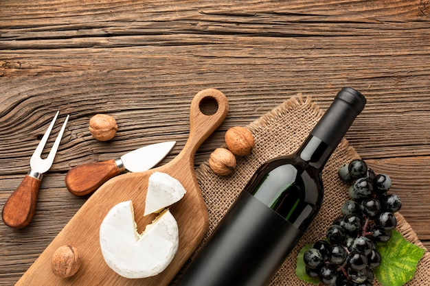 Camembert piatto disteso sul tagliere di legno uva e noci con utensili