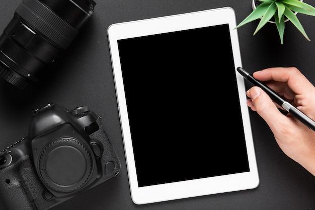 Disposizione piana della macchina fotografica e della compressa su fondo nero