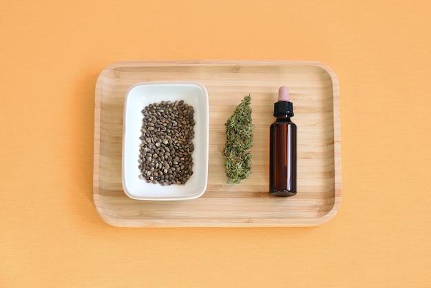 Lay piatto di semi di cbd in una ciotola, gemme per l'estrazione e una lattina di olio di cbd su uno sfondo di panno arancione.