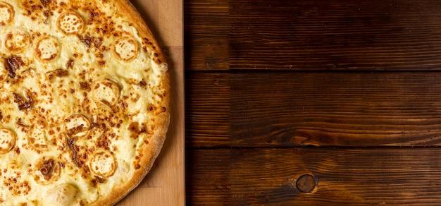 Pizza al formaggio piatto laici sul tagliere con copia-spazio