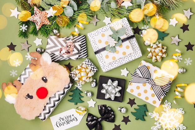 Sfondo di natale piatto con scatole regalo, nastri e decorazioni nei colori verde e nero
