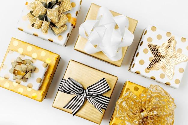 Sfondo piatto di natale o festa con scatole regalo e decorazioni in colori oro. disposizione piatta, vista dall'alto