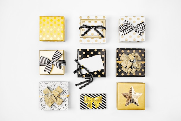 Sfondo piatto di natale o festa con scatole regalo, nastri, decorazioni nei colori oro e nero. disposizione piatta, vista dall'alto