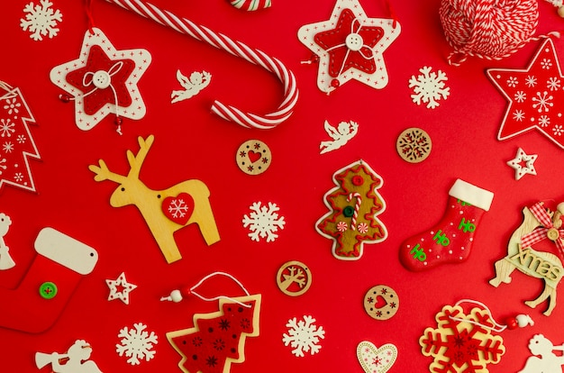 Modello di natale piatto laico fatto di decorazioni e giocattoli rossi per alberi di natale su uno sfondo rosso
