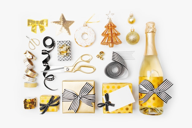 Set natalizio piatto con scatole regalo, bottiglia di champagne, fiocchi, decorazioni e carta da regalo nei colori oro e nero. disposizione piatta, vista dall'alto