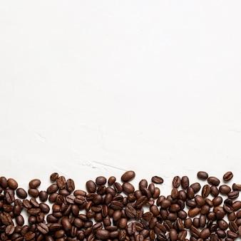 Chicchi di caffè piani di disposizione su fondo bianco con copia-spazio