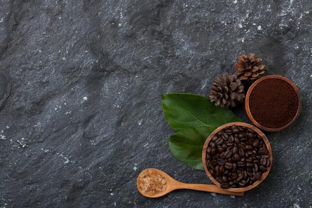 Chicchi di caffè piani di disposizione in tazza di legno sulla foglia verde, zucchero in cucchiaio di legno, pino sulla pietra nera