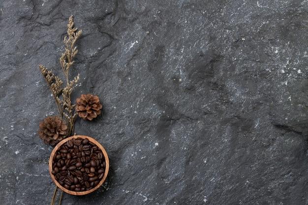 Chicchi di caffè piatti laici in tazza di legno, pino e fiori asciutti su struttura di pietra nera
