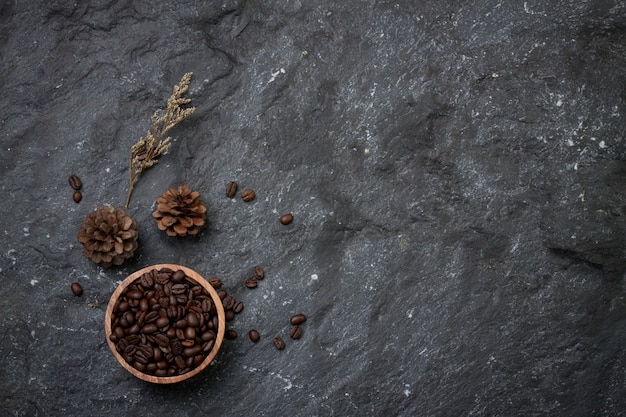 Chicchi di caffè piatti in tazza di legno, pino e fiori secchi su pietra nera