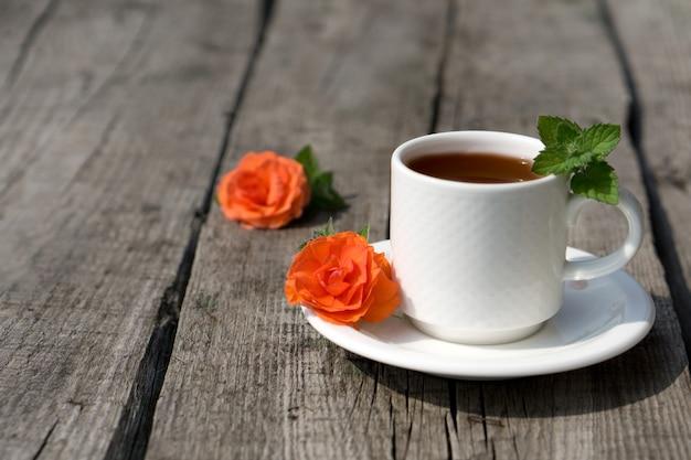 Composizione di caffè piatto laici con tazza bianca di caffè e fiori e foglia fresca di menta su fondo rustico in legno