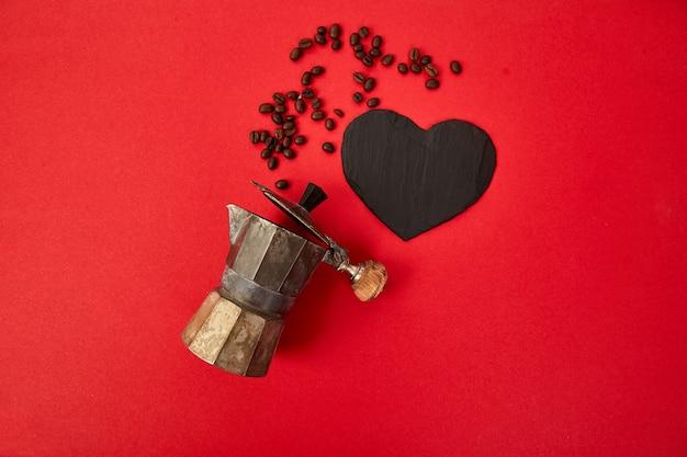 Disposizione piana della macchinetta del caffè e dei chicchi di caffè su fondo rosso.