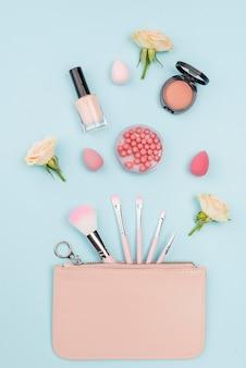 Collezione piatta laica di prodotti di bellezza su sfondo blu