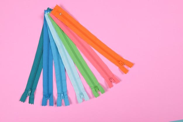Piatto lay di cerniera colorata per cucire su sfondo rosa, cucito e cucito concetto.