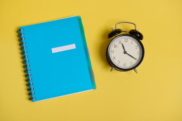 Composizione piatta di un blocco note colorato blu, organizzatore e sveglia, su sfondo giallo con spazio per il testo. ritorno a scuola e giornata degli insegnanti, ufficio e concetti aziendali