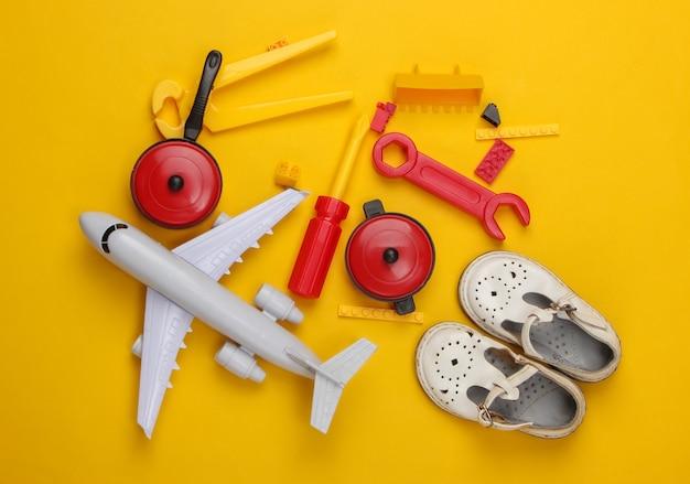 Composizione piatta laica di sandali per bambini e giocattoli su giallo.