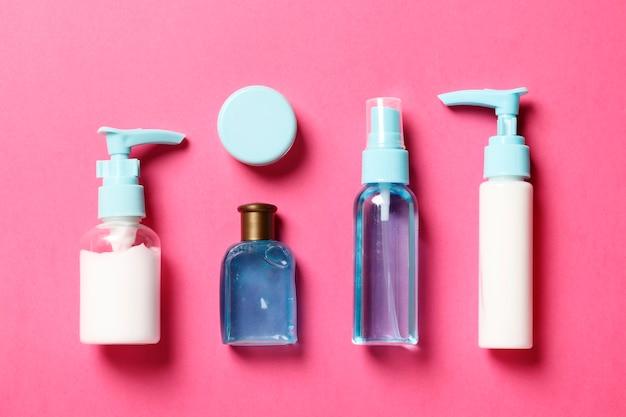 Cosmetici e crema di composizione piatta su uno sfondo rosa