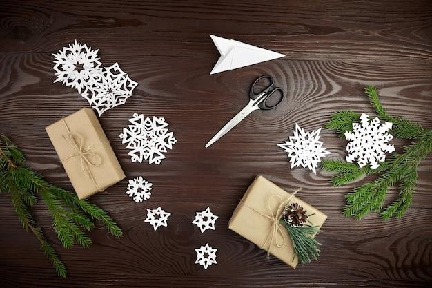 Composizione piatta per il taglio di fiocchi di neve di carta sul tavolo di legno