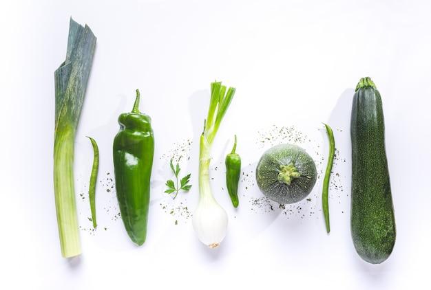 Composizione appartamento laica di verdure verdi su sfondo bianco.