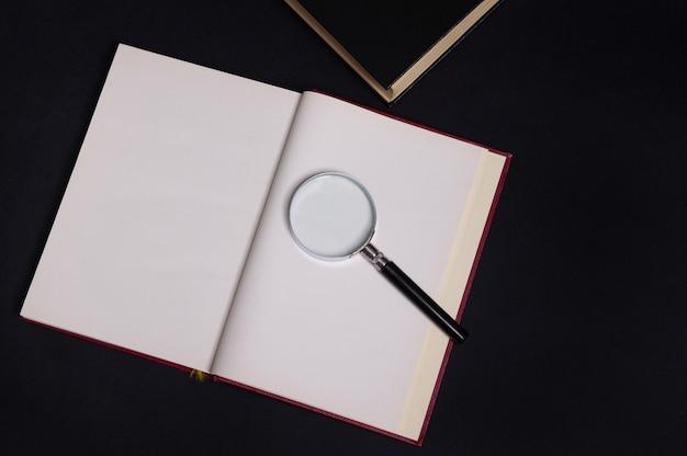 Composizione piatta di una lente di ingrandimento su un libro aperto con copertina rigida rossa, isolata su sfondo nero con spazio per il testo. concetto del giorno dell'insegnante, conoscenza, letteratura, lettura, erudizione