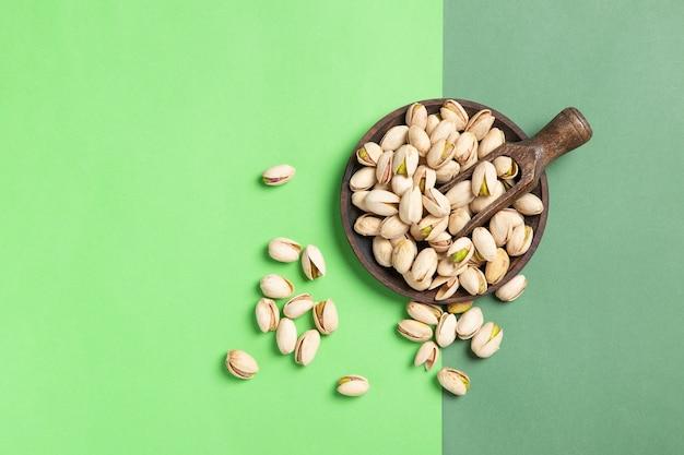 Composizione piatta laici di pistacchi sul cucchiaio di legno e piatto sul verde
